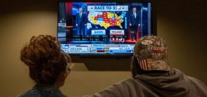 A couple watches the election results at a Republican watch party at Huron Valley Guns in New Hudson, Mich. People watching the results come in saw President Trump outperforming his position in preelection polls.