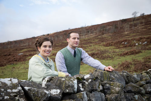 man and woman standing behind stone fence