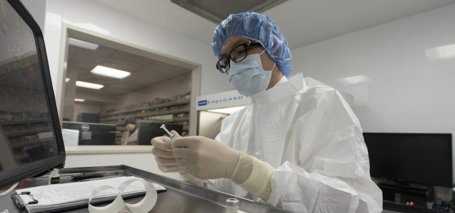 A pharmacist labels syringes in a clean room where doses of COVID-19 vaccines will be handled, Wednesday, Dec. 9, 2020, at Mount Sinai Queens hospital in New York.