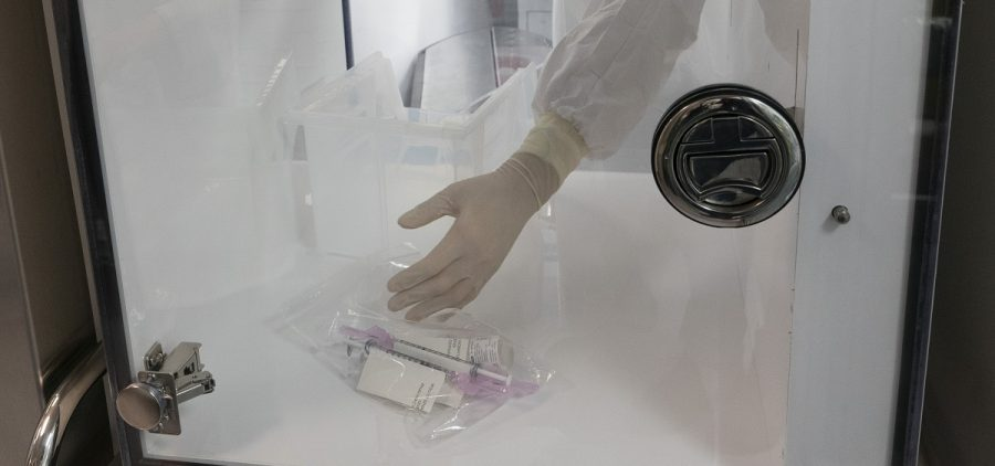 A pharmacist passes syringes from a clean room into the main pharmacy, Wednesday, Dec. 9, 2020 at Mount Sinai Queens hospital in New York.