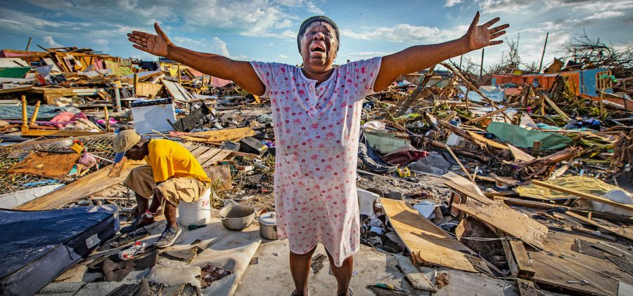 Aliana Alexis of Haiti stands on the concrete slab of what is left of her home