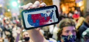 A supporter of President-elect Joe Biden holds up his mobile phone to display the Electoral College map outside the Philadelphia Convention Center after the 2020 presidential election is called on Nov. 7.