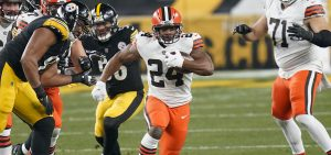 Cleveland Browns running back Nick Chubb (24) runs through a hole during the first half of an NFL wild-card playoff football game against the Pittsburgh Steelers, Sunday, Jan. 10, 2021, in Pittsburgh.