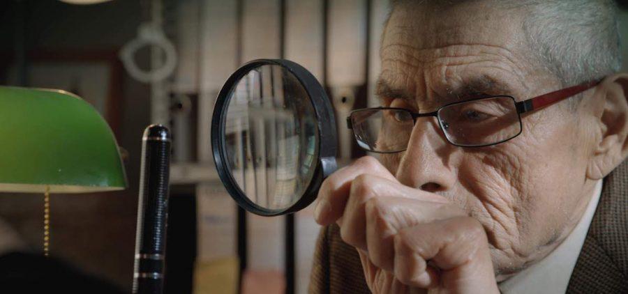 elderly man looking through magnifying glass