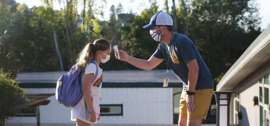 Nathan Grebil takes the temperature of a fourth-grader during a health screening in October at Bel Aire Elementary School in Tiburon, Calif.