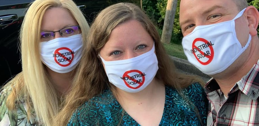 Adreanna Wills (center) and her husband (right) wearing masks with a logo opposing the local solar ordinance.