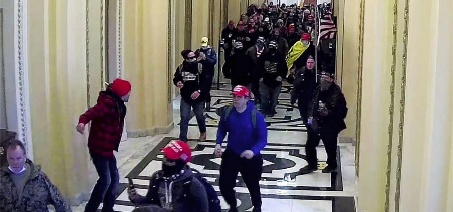 In this image taken from video footage released in a criminal complaint by the U.S. District Court for the District of Columbia, Alexander Sheppard, center, joins other rioters who stormed the U.S. Capitol on Jan. 6, 2021, in Washington.