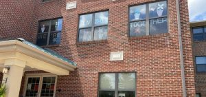 """Signs reading """"We're all in this together"""" decorate the windows of a nursing home facility in northeast Columbus."""