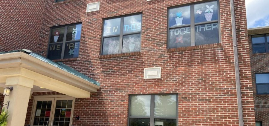 "Signs reading ""We're all in this together"" decorate the windows of a nursing home facility in northeast Columbus."