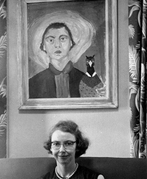Flannery O'Connor sitting under painting of herself