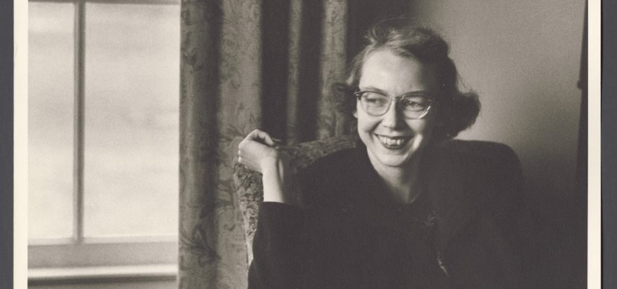 Black and white of Flannery O'Connor in front of window