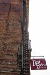 Several cracks are visible along the brick wall of a building in uptown Athens that was evacuated Friday because of safety concerns.