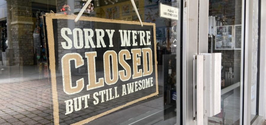 A closed sign hangs in the window of a business