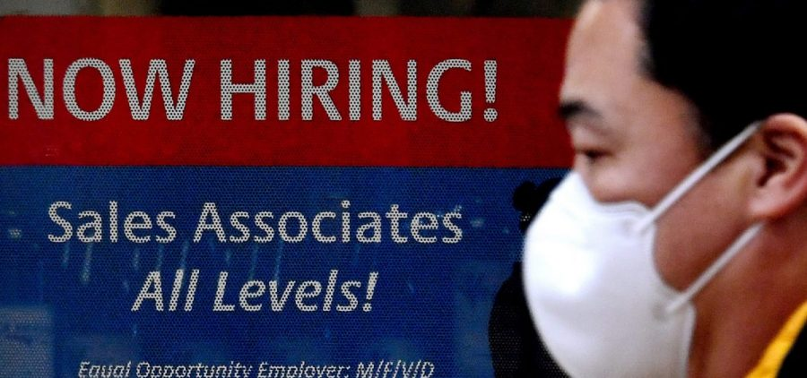 """A man walks past a """"Now Hiring"""" sign in front of a store in early December in Arlington, Va. U.S. employers added 379,000 jobs in February, as hiring picked up sharply from the previous month."""