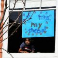 """Jeevan Guha, 6, poses for a portrait near his homemade sign in San Francisco. His sign reads, """"I miss my school."""""""