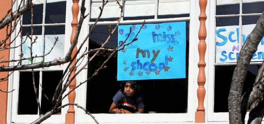 "Jeevan Guha, 6, poses for a portrait near his homemade sign in San Francisco. His sign reads, ""I miss my school."""