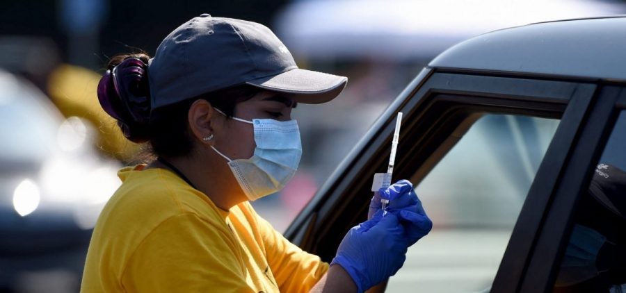 A worker prepares to give a COVID-19 vaccine at the Dignity Health Sports Park in Carson, Calif. on March 18, 2021.