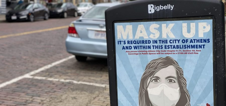 A mask up sign on a trash can on Court Street in Athens