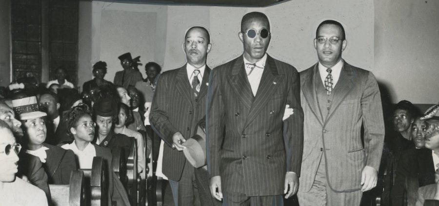 Leroy Carter (left) and Donald Jones, NAACP assistant field secretary (right), escort Sergeant Isaac Woodard (center) down an aisle. Likely taken while Woodard was on his speaking tour with the NAACP. 10/26/1946.
