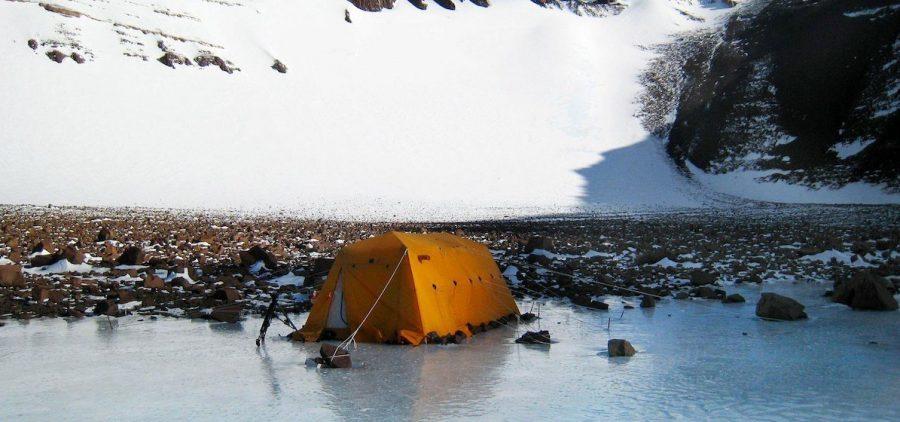 research tent near rocky shore and glacier