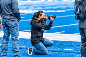 Dean taking photos on sideline at football game