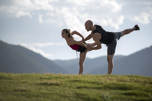 Man and Woman practicing skating lifts in grass