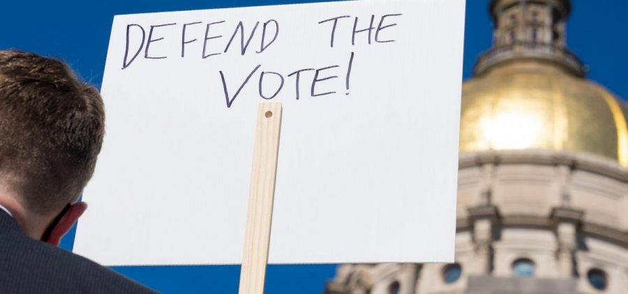 Demonstrators protest House Bill 531 last month in Atlanta. The legislation signed into law has drawn criticism from voting rights activists and businesses, who say it limits access to the polls and disproportionately harms voters of color.