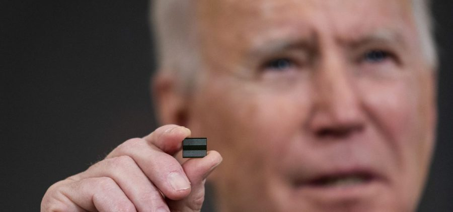 President Biden holds a semiconductor during remarks before signing an executive order on the economy at the White House on Feb. 24. On Monday, senior members of his team will meet with leaders across various industries to discuss a shortage of semiconductors.
