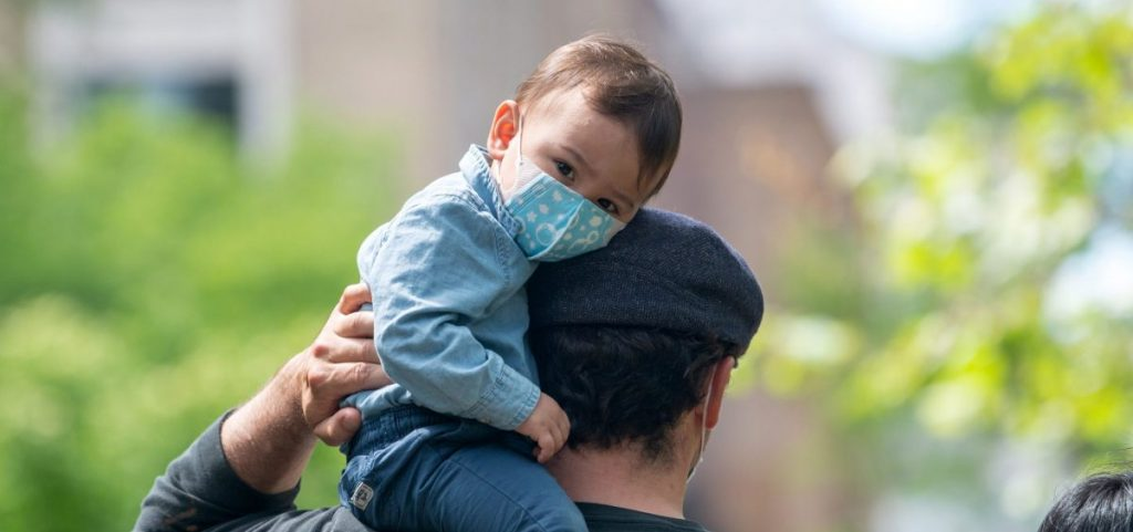 A child sits on his father's shoulder in New York City's Central Park in May 2020. The COVID-19 vaccine isn't presently available to those under 16, raising questions for parents and their kids.