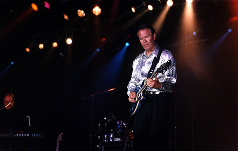 Glen Campbell playing guitar on stage