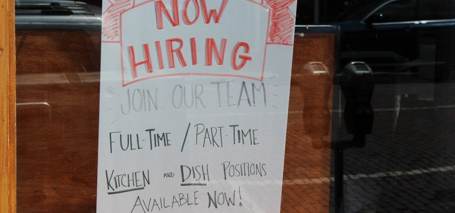 "A bar and restaurant in Athens with a ""Now Hiring"" sign in the window."