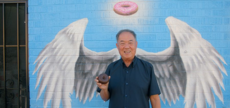 Ted Ngoy at DK Donuts. Photo taken in front of painted wings on wall to make it look like an angel