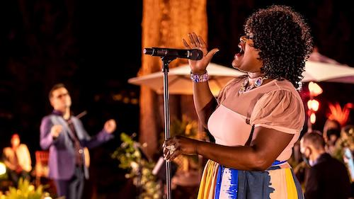 female singer on stage with band, conductor in background