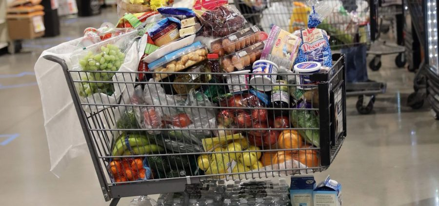 A shopper's cart is full in the checkout line at a ShopRite supermarket in April 2020 in Plainview, N.Y. A year later, prices for most goods have jumped, according to government data, as companies struggle to secure critical raw materials amid supply constraints.