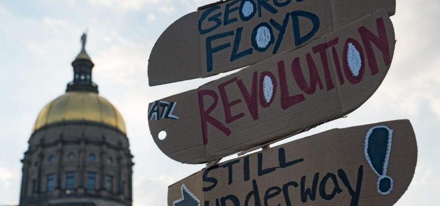 People gather to memorialize the life of George Floyd on the first anniversary of his death on Tuesday in Atlanta. America's corporations pledged to boost diversity soon after his death last year, but progress can be slow.
