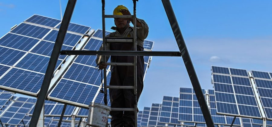 Workers next to solar panels in an integrated power station in Yancheng, China, in October. An unprecedented amount of renewable power came online in the fourth quarter of 2020, according to a new report from the International Energy Agency. China alone added more than 92 gigawatts of capacity, more than triple the amount it added in the fourth quarter of 2019.