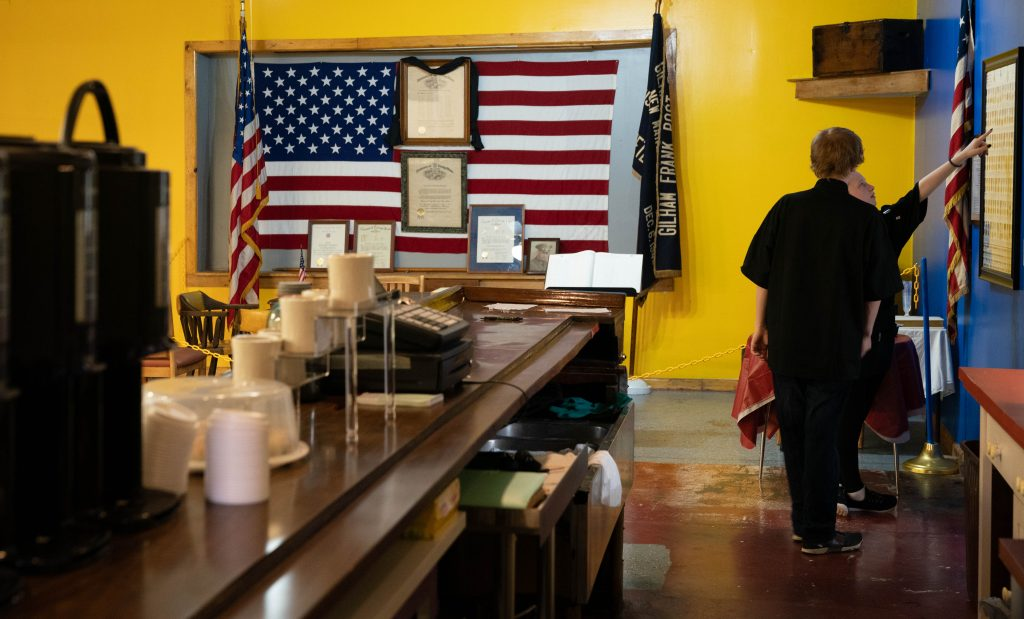 Sineka Brooks, right, 17, and Richie Goins, employees of the newly opened Bailey Mae Trailhead Cafe, look at a service medal poster while waiting for customers during the cafe's grand opening, in Chauncey, Ohio, on Monday, June 7, 2021. Bailey Mae's is the new home to VFW Post 8804, which previously was located in New Marshfield, Ohio, and operated in that location for over 24 years before that location shut down.