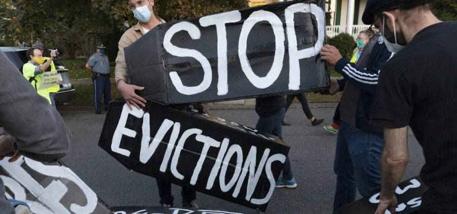 Housing activists erect a sign in front of Massachusetts Gov. Charlie Baker's house in Swampscott, Mass. on Oct. 14, 2020. The Centers for Disease Control and Prevention has extended a moratorium on evictions until the end of July.