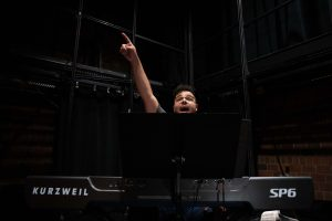 Devin Sudman, music director for Ohio Valley Summer Theater, sings along with other performers during a rehearsal for the theater company's 70th anniversary celebration performance, in Athens, Ohio, on Thursday, July 8, 2021. [Joseph Scheller | WOUB]