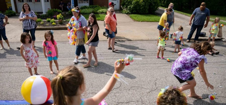 Members of the Hopewell Health Centers float in the Founders Day parade toss candy and mini-beach balls to attendees in Coolville, Ohio, on Saturday, July 10, 2021. [Joseph Scheller | WOUB]