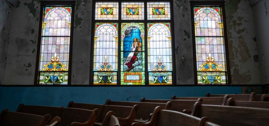 Doctor Tee Ford-Ahmed poses for a portrait next to the stain-glass window inside of the Mt. Zion Baptist Church that has since become the symbol for the church, in Athens, Ohio, on Wednesday, July 21, 2021. [Joseph Scheller | WOUB]