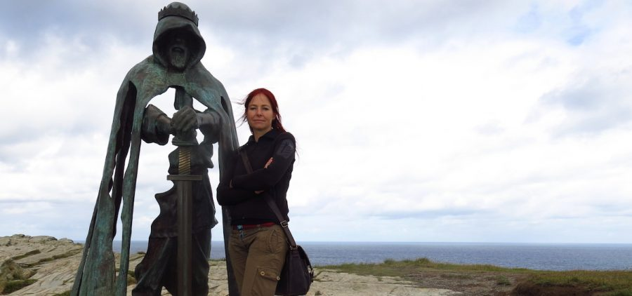 archeoloist standing with stature of king arthur
