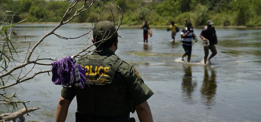 A Border Patrol agent watches as a group of migrants walk across the Rio Grande on their way to turning themselves in upon crossing the U.S.-Mexico border in Del Rio, Texas.
