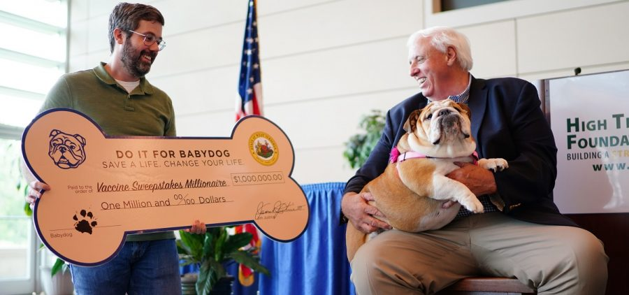 In this image provided by the West Virginia Governor's Office, Timothy Jackson, the latest million-dollar winner in West Virginia's vaccination sweepstakes, poses with West Virginia Gov. Jim Justice