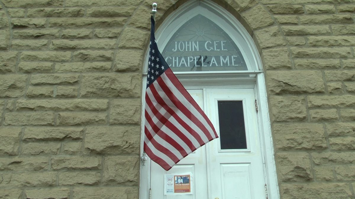 Front of the John Gee Black Historical Center building with American Flag blowing in front of it.