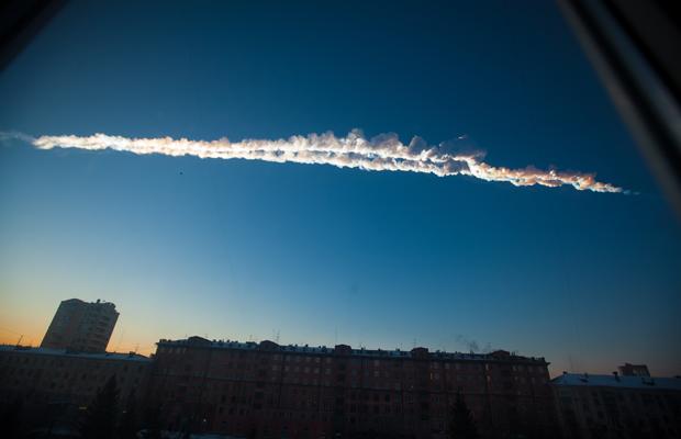 white smoke trail of meteor across blue sky