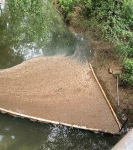 Booms were placed in Raccoon Creek to help collect grease and sewage that migrated into the water from a nearby field used for dumping.