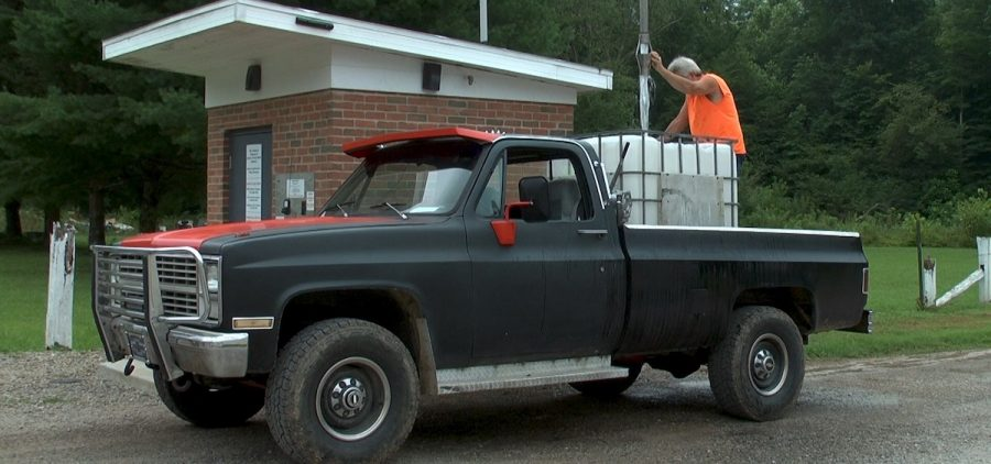 A man pours water from a water dispensary into the back of his truck