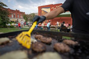 Dane Salabak lifts a burger off the grill while volunteering for the Radical Times Thursday Night Dinner grand opening in Nelsonville, Ohio, on Thursday, Aug. 5, 2021. [Joseph Scheller   WOUB]