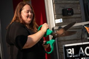 Dottie Fromal cuts the ribbon at the grand opening of the new location for the Radical Times, in Nelsonville, Ohio, on Thursday, Aug. 5, 2021. [Joseph Scheller   WOUB]